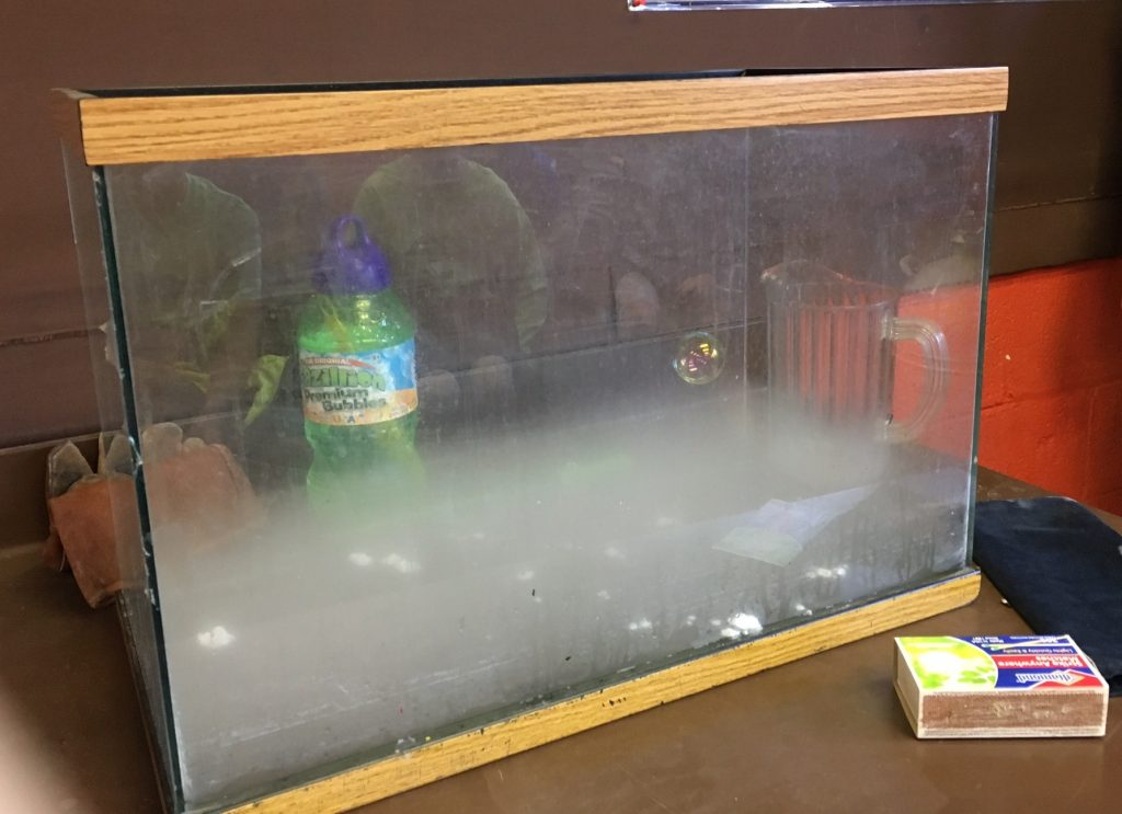 Create CO2 gas with dry ice and water. Demonstrate that CO2 is more dense than air by blowing bubbles.